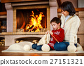 Mother and her little son by a fireplace at home 27151321