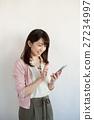 ผู้หญิงในวัยยี่สิบของพวกเขาโดยใช้สมาร์ทโฟน 27234997