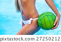Sexy girl near the pool holding green ball 27250212