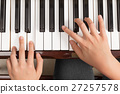 Top view close up of female hands playing piano 27257578