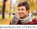 man recording voice on smartphone at autumn park 27294291