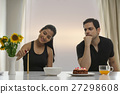 Serious man looking at woman lighting candle at table with cake 27298608