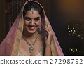 Woman in bridal dress smiling while looking away 27298752