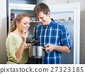 Happy couple standing near refrigerator 27323185