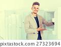 man choosing new refrigerator 27323694