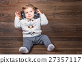 infant boy listen music with headphones 27357117