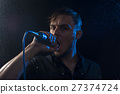 Portrait of attractive man singing into microphone 27374724
