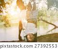 Dad holding son upside down in park under sunlight 27392553