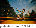 Couple jumping on trampoline in the park 27414113