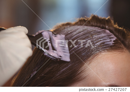 Hairdresser dyeing hair of her client 27427207