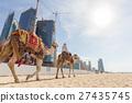 Man offering camel ride on Jumeirah beach, Dubai 27435745