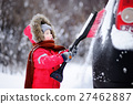 Cute little child helping to brush a snow from a car 27462887