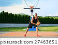 Young man on basketball court dribbling with ball. 27463651