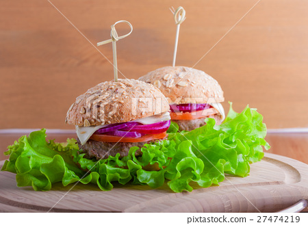 Cheeseburger with tomato, onion and green salad 27474219