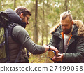 Man with a beard and his friend hiking in a forest 27499058