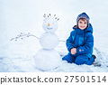 little boy sitting near the smiling snowman 27501514