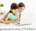 happy Little girl looking at laptop  with her mother 27529025