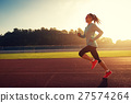 Young woman runner running on stadium track 27574264