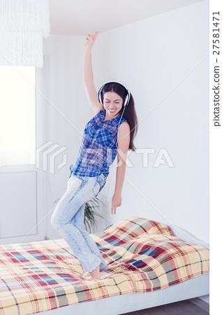 girl in headphones dancing on the bed 27581471