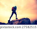 hiker jumping on seaside mountain peak rock 27582515