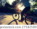 young asian woman riding bike on forest trail 27582589