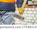 Worker with sledgehammer near to brick wall 27588314