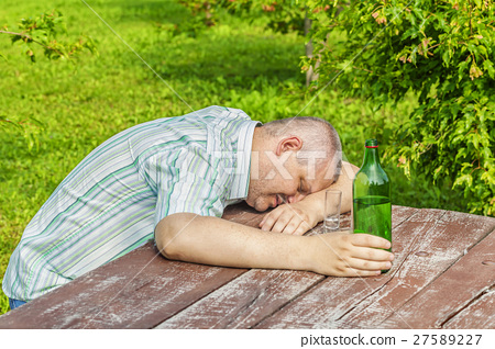 Drunk man sleeping near bottle of alcohol on table 27589227