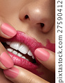 Fingers spreading pink lipstick on mouth 27590412