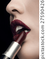 Woman applying red lipstick on black background 27590426