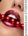 Open mouth with red liptisck biting red pearls 27590430