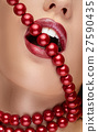 Mouth with red lipstick biting red pearls 27590435