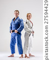 The two judokas fighters posing on gray 27594429