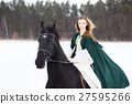Young girl in white dress and cape riding horse 27595266