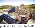 Father playing with baby son as lying at the beach 27621505