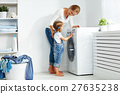 family mother and child girl  in laundry room near washing machi 27635238