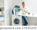 happy woman housewife in the laundry room near the washing machi 27635242