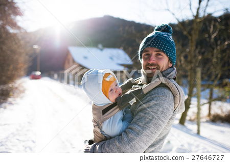Father holding his son in baby carrier. Sunny 27646727