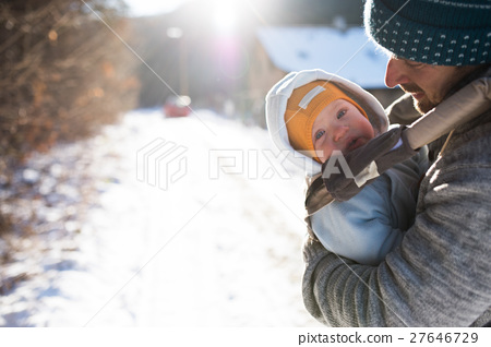 Father holding his son in baby carrier. Sunny 27646729