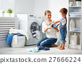 family mother and child girl  in laundry room near washing machi 27666224
