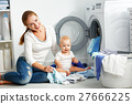 mother housewife with baby engaged in laundry fold clothes into 27666225