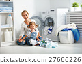family mother and child girl  in laundry room near washing machi 27666226