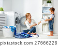 family mother and child girl  in laundry room near washing machi 27666229