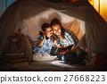 mother and child daughter with a book and a flashlight before go 27668223