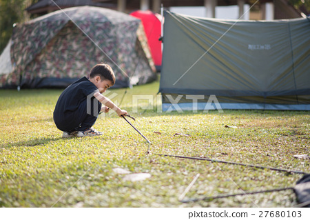 Little boy building a tent for camping with family holiday summer time 27680103
