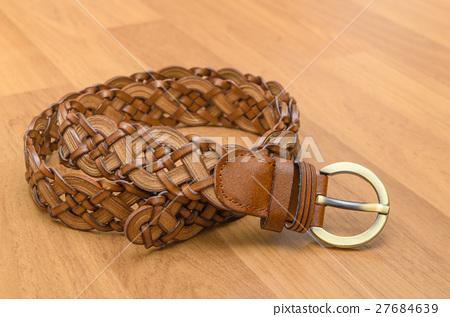 Brown women belt on wooden floor 27684639