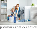 family mother and child girl  in laundry room near washing machi 27777179