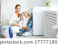 mother housewife with baby engaged in laundry fold clothes into 27777180