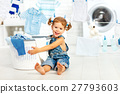 child fun happy little girl to wash clothes in laundry room 27793603