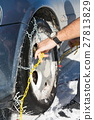 Man mounting snow chains on wheels 27813829