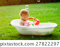 little baby girl bathes in bath on meadow 27822297